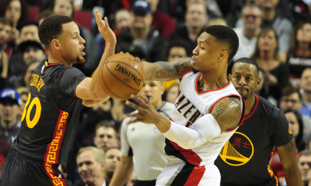 Feb 19, 2016; Portland, OR, USA; Portland Trail Blazers guard Damian Lillard (0) passes the ball on Golden State Warriors guard Stephen Curry (30) during the first quarter of the game at the Moda Center at the Rose Quarter. Mandatory Credit: Steve Dykes-USA TODAY Sports