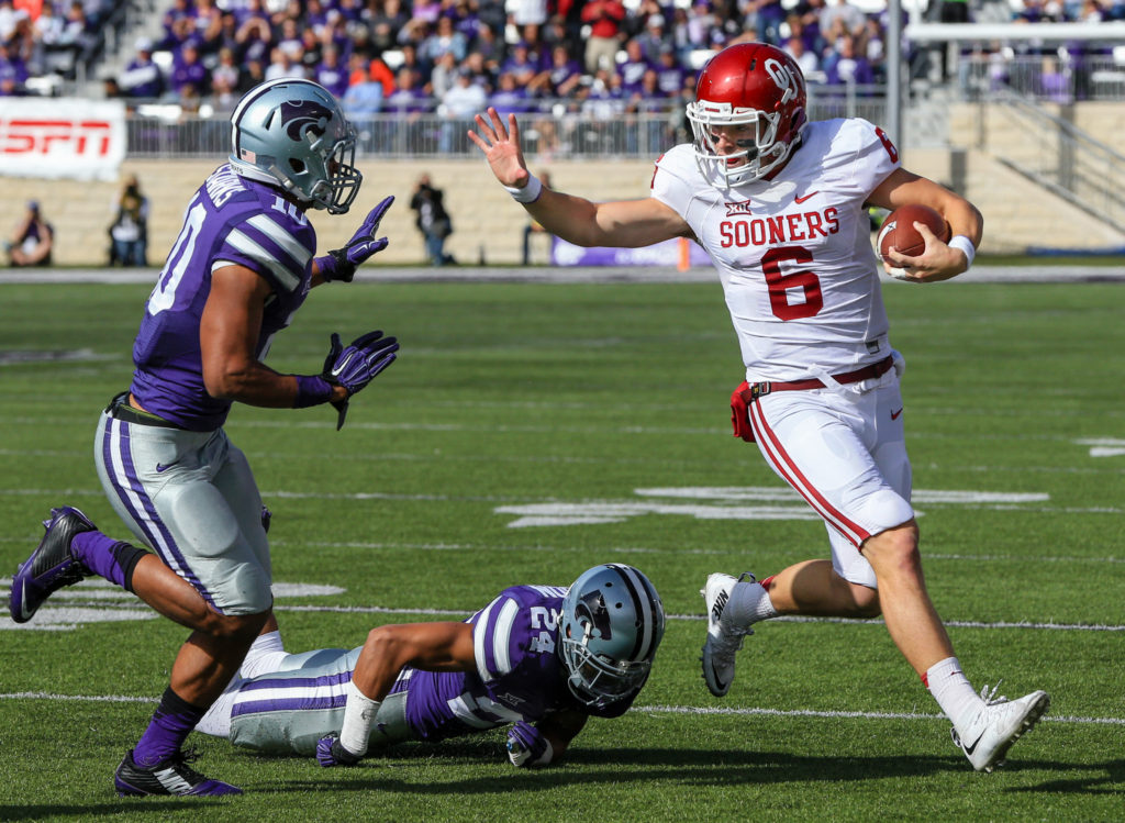 Oklahoma quarterback Baker Mayfield (6) runs away from Kansas State defensive backs Nate Jackson, bottom, and Donnie Starks (10) during the first half of an NCAA college football game in Manhattan, Kan., Saturday, Oct. 17, 2015. (AP Photo/Nati Harnik)